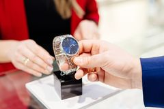 Young elegant man buying wrist watch in jewelry store. Customer service in jewelry store stock photos