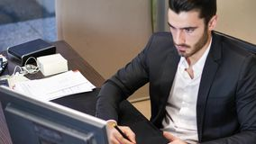 Concentrated man using graphic tablet in office stock video footage
