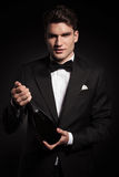 Young elegant man holding a bottle of wine Royalty Free Stock Image