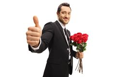 Young elegant man holding a bunch of roses and showing thumbs up royalty free stock images