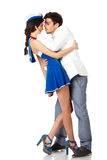 Young elegant man kissing sailor woman. Full body shot of elegant young manseducing sailor woman. Isolated on white background. High resolution studio image Royalty Free Stock Photography