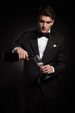 Young elegant man pouring wine in a glass. While looking down Stock Photos