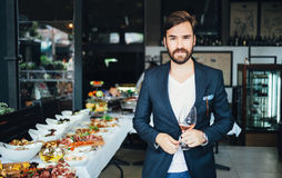 Young elegant man standing in the restaurant, holding a glass of wine. Man's style Royalty Free Stock Photo