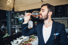 Young elegant man standing in the restaurant, holding a glass of wine. Man's style. N Stock Photos