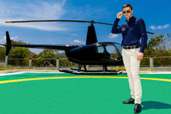Young elegant man wearing sunglasses standing next to a private. Helicopter Royalty Free Stock Images