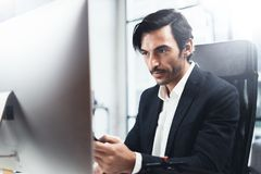 Young elegant man working at sunny office on desktop computer while sitting at wooden table.Blurred background stock photography