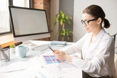 Financial analyst. Young elegant office manager scrolling in smartphone while sitting by desk and working with financial documents stock photos