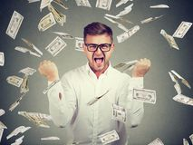 Excited man in flying money bills. Young elegant and smart man posing victoriously in†flying dollar bills Royalty Free Stock Photos