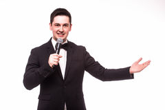 Young elegant talking man holding microphone and present invisible product. Stock Images