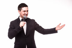 Young elegant talking man holding microphone and present invisible product. Royalty Free Stock Images