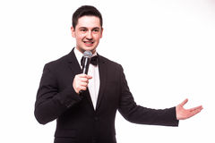 Young elegant talking man holding microphone and present invisible product. Royalty Free Stock Image