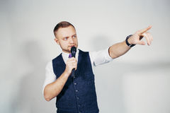 Young elegant talking man holding microphone talking with pointing finger. Isolated on grey background. stock photography