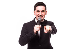 Young elegant talking man holding microphone talking with pointing finger. Stock Photography