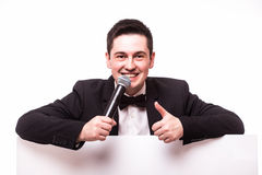 Young elegant talking man holding microphone talking on table  with hands sign. Stock Photo
