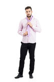 Young elegant well dressed man in pink shirt adjusting and tying pink necktie knot Royalty Free Stock Photos