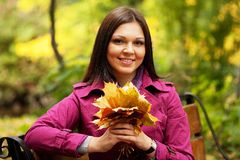 Young elegant woman with autumn leaves Stock Images