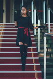 Young elegant woman in black dress walking on stairs with the red carpet Stock Photo