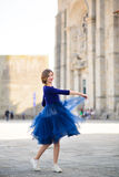 Young elegant woman in blue long flying dress posing at stairway against old city building Stock Photo