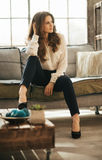 Young elegant woman with brown hairs sitting in loft apartment Stock Photos