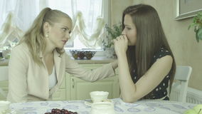 Young elegant woman comforting sad friend at home during tea time