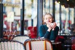 Young elegant woman drinking coffee in cafe in Paris, France Royalty Free Stock Photo