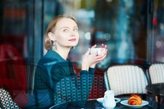 Young elegant woman drinking coffee in cafe in Paris, France Royalty Free Stock Images