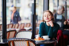 Young elegant woman drinking coffee in cafe in Paris, France Stock Photo