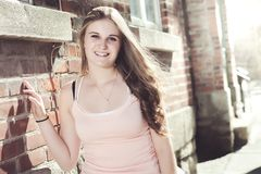 Young elegant woman in front of brick wall Royalty Free Stock Photo