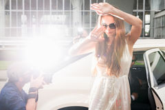Young elegant woman hiding her face from paparazzi as she arrive Royalty Free Stock Images