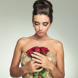 Young elegant woman looking down at red roses Stock Photography