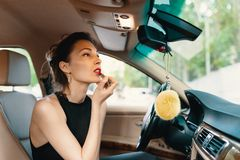 Free Young Elegant Woman Looking In The Car View Mirror While Applying Makeup, Lipstick On The Lips Stock Photos - 166166283
