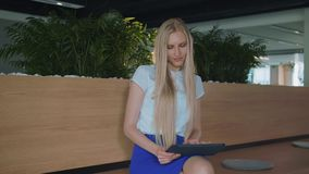 Relaxing woman with tablet in office. Young elegant woman sitting barefoot on wooden tribune in modern office using. Young elegant woman sitting barefoot on stock footage