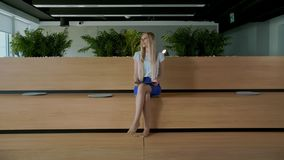 Relaxing woman with tablet in office. Young elegant woman sitting barefoot on wooden tribune in modern office using. Young elegant woman sitting barefoot on stock video footage