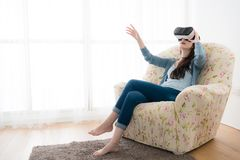 Young elegant woman sitting on sofa chair. Wearing virtual reality goggles looking online website and using hand moving 3D simulation screen Royalty Free Stock Photography