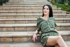 Young elegant woman sitting on stone steps Royalty Free Stock Image