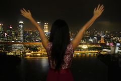 Young elegant woman spreading arms free at top floor rooftop bar in front of amazing beautiful view of city lights at night stock photography