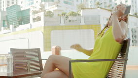 Young elegant woman waiting for boyfriend on terrace near swimming pool. City landscape in background. Young elegant woman waiting for boyfriend on terrace near stock video footage