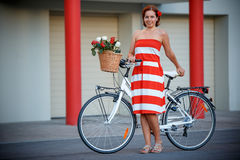 Young elegantly dressed woman with bicycle and a Royalty Free Stock Photography