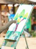 Young elephant drawing a picture. Of a tree with color paint royalty free stock image