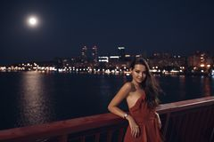 Young ellegant woman standing on the ligths of the night city background. Freedom and girl in love concept royalty free stock photography