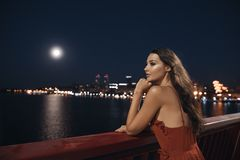 Young ellegant woman standing on the ligths of the night city background. Freedom and girl in love concept stock photography