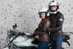 Young embracing couple in a motorcycle outfit standing together near the motorbike in the garage Royalty Free Stock Image