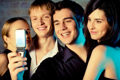 Young embracing smiling people taking photograph by cellphone. And posing at celebration or night party Stock Images
