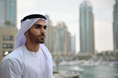 Young Emirati arab man standing by the canal. In Dubai Marina Stock Image