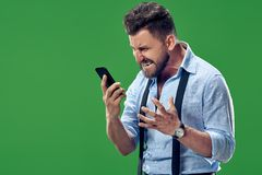 The young emotional angry man screaming on green studio background. Screaming, hate, rage. Crying emotional angry man with mobile phone screaming on green studio Royalty Free Stock Images