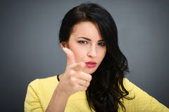 Young emotional beauty woman pointing you, standing on gray background Royalty Free Stock Photo