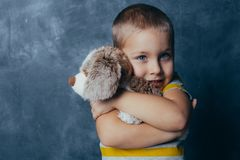 A young emotional boy holds in hands a soft toy dog standing on a blue studio background stock images