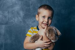 A young emotional boy holds in hands a soft toy dog standing on a blue studio background stock photo