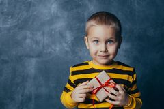 A young emotional boy holds in his hands a gift with a red bow standing on a blue studio background royalty free stock photos
