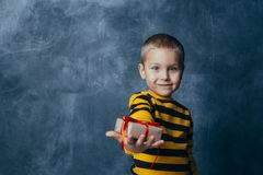 A young emotional boy holds in his hands a gift with a red bow standing on a blue studio background stock photos